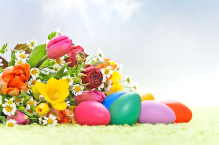 a bunch of spring flowers with easter eggs in a artificial landscape