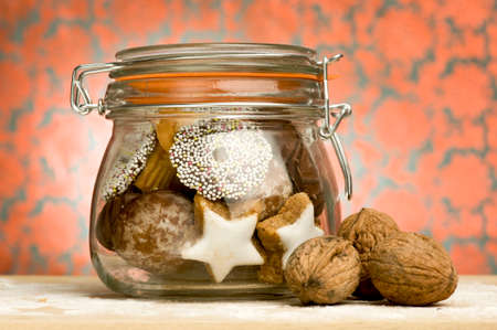 preserving glass jar containing christmas cookies decorated with wallnut