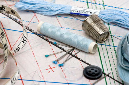 measured: sewing thread with needle, thimble and pattern in light blue Stock Photo