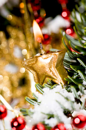 close up on a golden, star shaped candle, burning in a christmas tree photo
