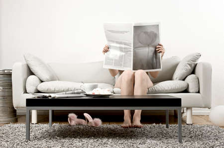 woman sitting on a couch and reading a newspaper photo