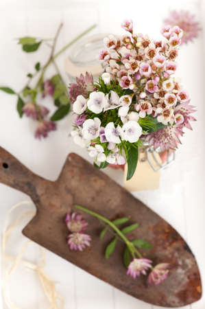 a bunch of flowers and a rusty spade