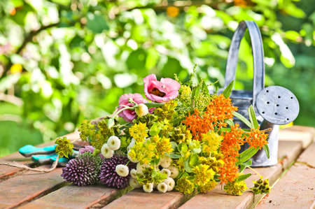 floristics: a bunsh of flowers from the garden on a table with a metal water can Stock Photo