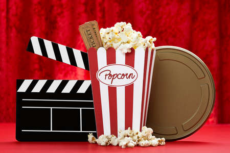 a bag of popcorn, cinema tickets, a black clapper board and a golden film can with red background