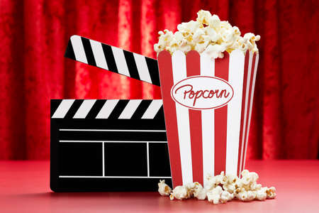 a bag of popcorn and a black clapper board with red background