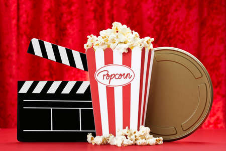 a bag of popcorn, a black clapper board and a golden film can with red background