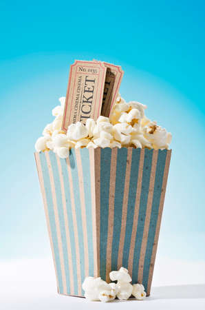 a bag of popcorn and cinema tickets with blue background