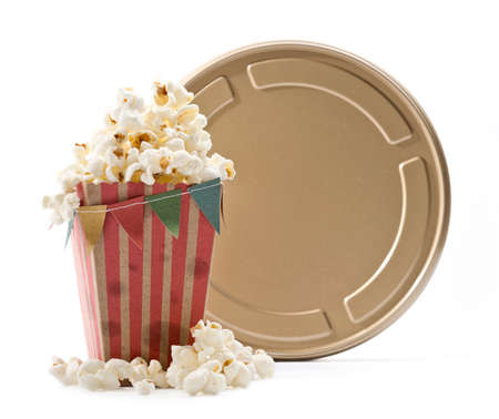 a bag of popcorn with little flags and a golden film can with white background Stock Photo