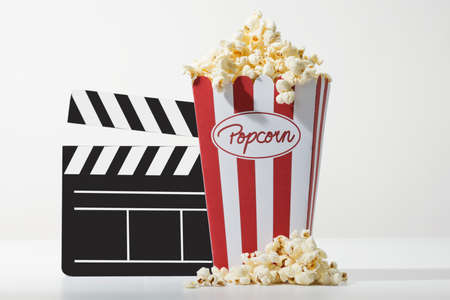 a bag full of popcorn  and a black clapper board with white background