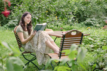 chair: young woman sitting in the garden, reading in the summer