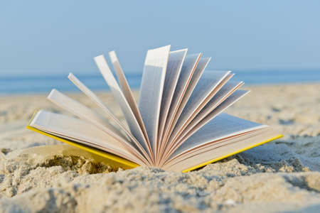 an open book in the sand at the beach