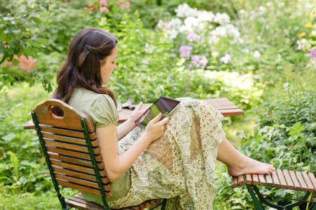 young woman sitting in the garden, reading an e-book