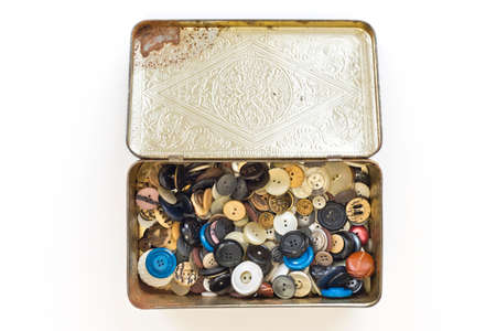a collction of old buttons in a tin box, isolated photo