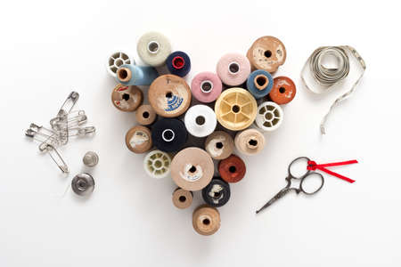 savety: a collection of thread spools in a heart shape on white background with accessories Stock Photo