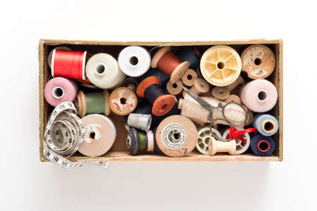 savety: a collection of thread spools in a woodn box on white background with accessories