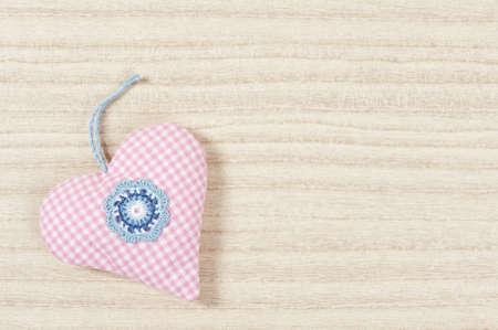 nger: Stoff-Herz mit Häkelblumen auf hellem Hintergrund