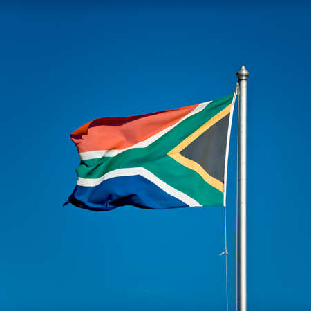 nicely: South African flag in the wind with blue sky