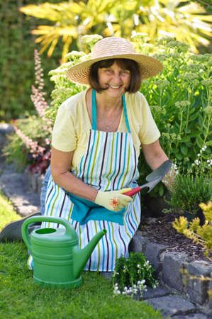 a woman working in a garden planting plants, summer time photo