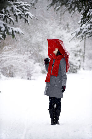 Woman in the snow with a red umbrella