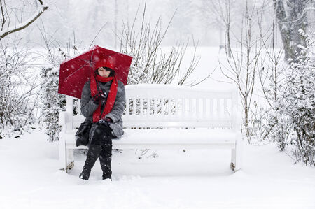 Woman in the snow with a red umbrella sitting on a bench