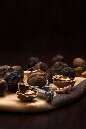 stil: walnuts on a wooden board with a nutcracker on dark background Stock Photo
