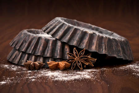 old backing dish with flour and anise seeds on dark background Stock Photo
