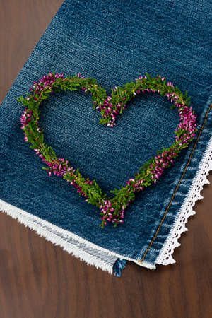 erica: heart shape from erica flowers on jeans and wooden background