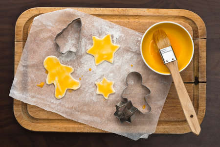 cutters: a wooden board with cookies, egg yolk and cookie cutters