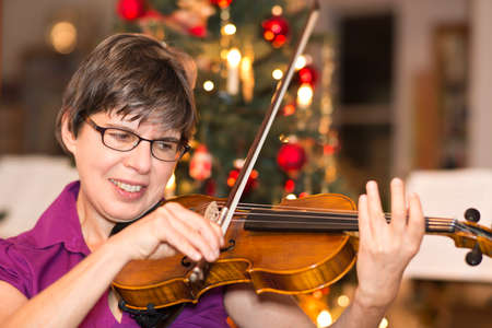 solo  christmas: a woman playing the violin in front of a christmas tree at home