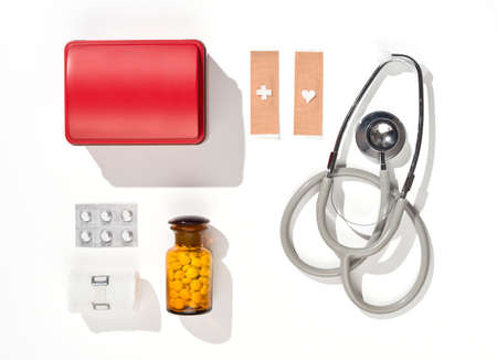 a first aid kit with pills and a stethoscope plasters on white background photo