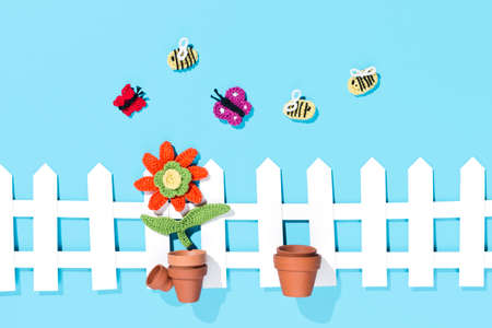 crochet flower in a pot with white fence Butterlfies and bees on blue background