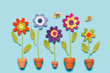 colorful crochet flowers in a pot with bees on blue background