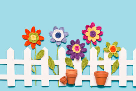 crochet flowers behind a white paper fence with flower pots on blue background