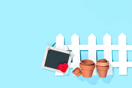 white paper fence with flower pots and a tagwith a crochet red heart on blue background Stock Photo