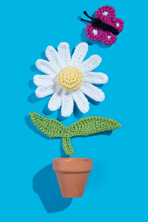 crochet daisy in a pot with butterfly on blue background