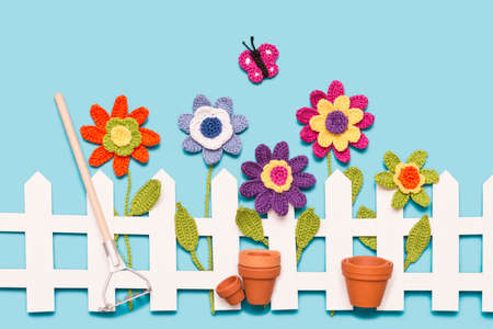 crochet flowers behind a white paper fence with a butterfly, flower pots and a rake on blue background Stock Photo