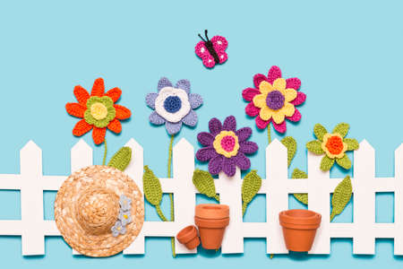 crochet flowers behind a white fence with a paper butterfly flower pots and a hat on blue background Stock Photo
