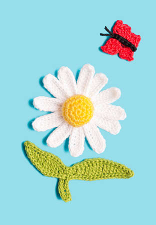 crochet daisy with a butterfly on blue background