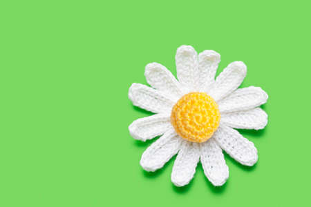 crochet daisy on green background