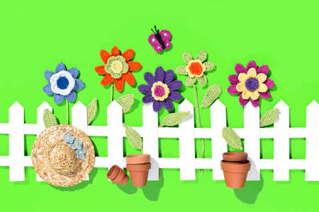 crochet flowers behind a white fence with a paper butterfly flower pots and a hat on green background