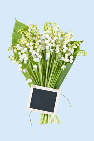 a bouquet of Lilies of the Valey with a tag on a light blue background