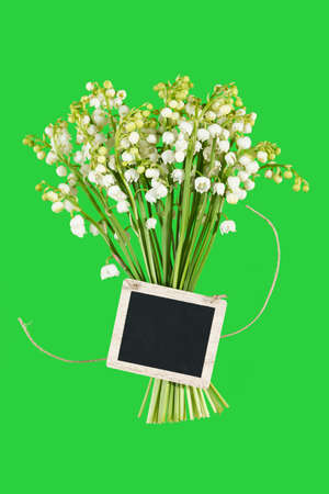 a bouquet of Lilies of the Valey with a tag on a green background Stock Photo