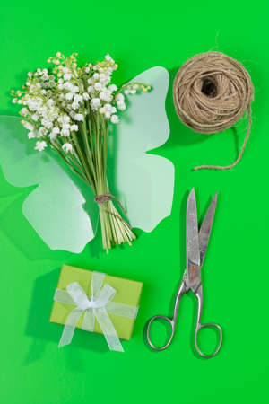 A bouquet of lily of the valley with a plastic butterfly present a scissors and a cord on green background top view Stock Photo