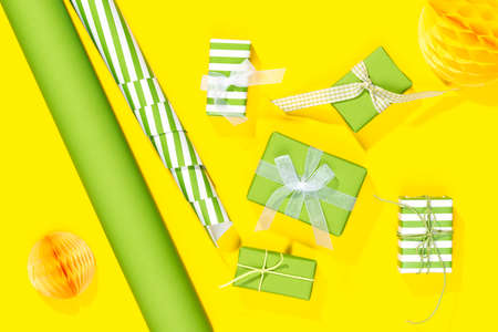fife small presents with wrapping paper on yellow background Stock Photo