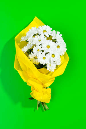 a bouquet of daisies in a yellow paper wrapping on green background