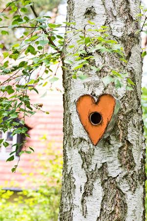 a orange, heart shaped birdhouse hanging on a tree Stock Photo
