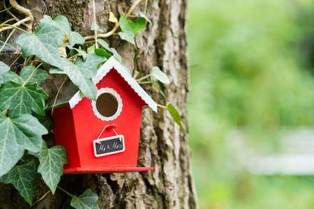 mrs: una casa para p�jaros rojo colgando de un �rbol en el jard�n con un letrero que dec�a Mr. & Mrs.