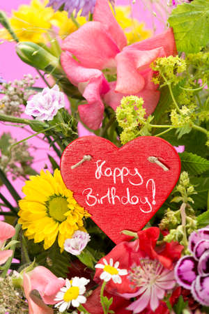 magenta decor: a close up of a bouquet of flowers with a red, heart shaped label saying: Happy Birthday! and a magenta gradiant background