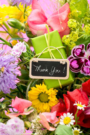 thee: a close up of a bouquet of flowers with a black label saying: Thank You!, thee candles on magenta paper