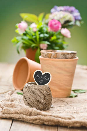 mr and mrs: flowers with decoration, green background, on a table and a black heart shaped tag saying: Mr & Mrs Stock Photo
